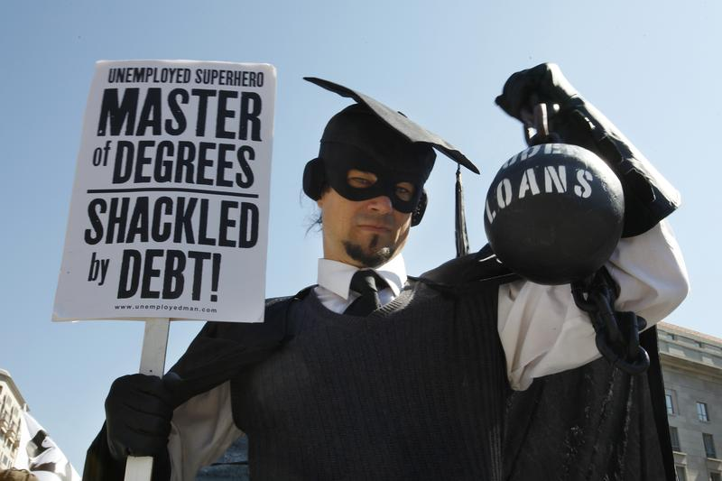 """In this Oct. 6, 2011 photo, Gan Golan, of Los Angeles, dressed as the """"Master of Degrees,"""" holds a ball and chain representing his college loan debt, during Occupy DC activities in Washington."""