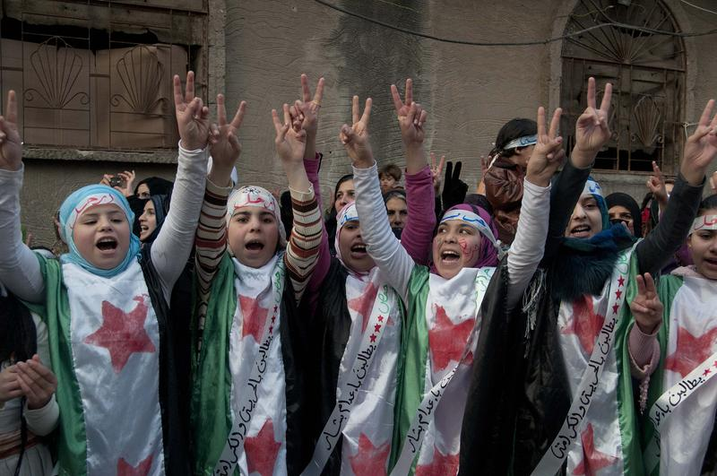 In this photo taken on Wednesday Dec. 21, 2011, anti-Syrian regime protesters flash the victory sign as they wear Syrian revolution flags during a demonstration in the Baba Amr area, in Homs province.