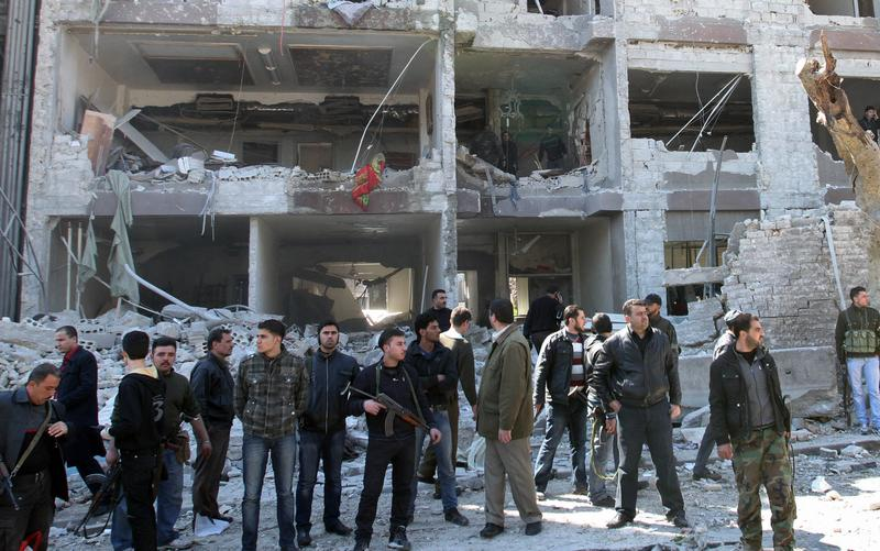 Syrian security officers gather in front the damaged building of the aviation intelligence department, which was attacked by one of two explosions, in Damascus, Syria, on Saturday, March 17, 2012.
