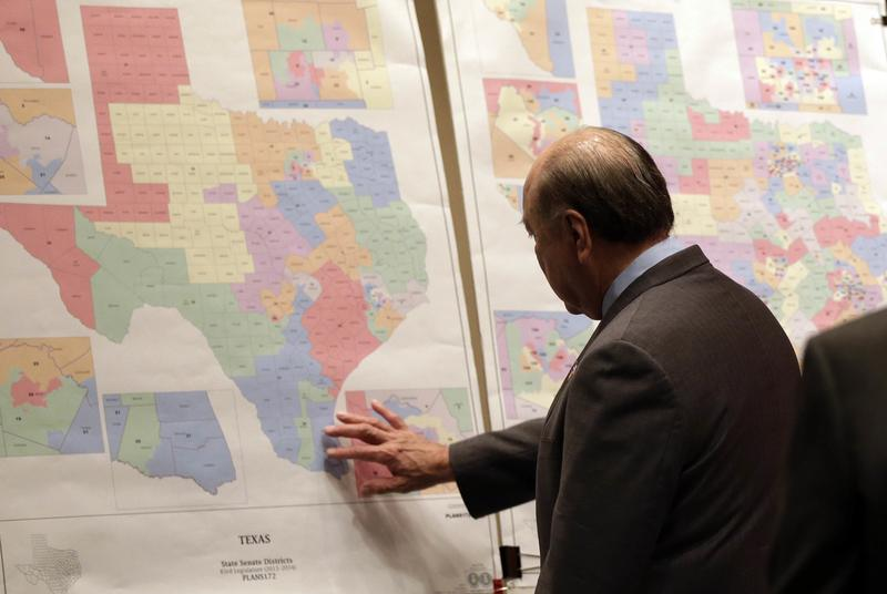 """Texas state Sen. Juan """"Chuy"""" Hinojosa looks at maps on display prior to a Senate Redistricting committee hearing in Austin, Texas."""