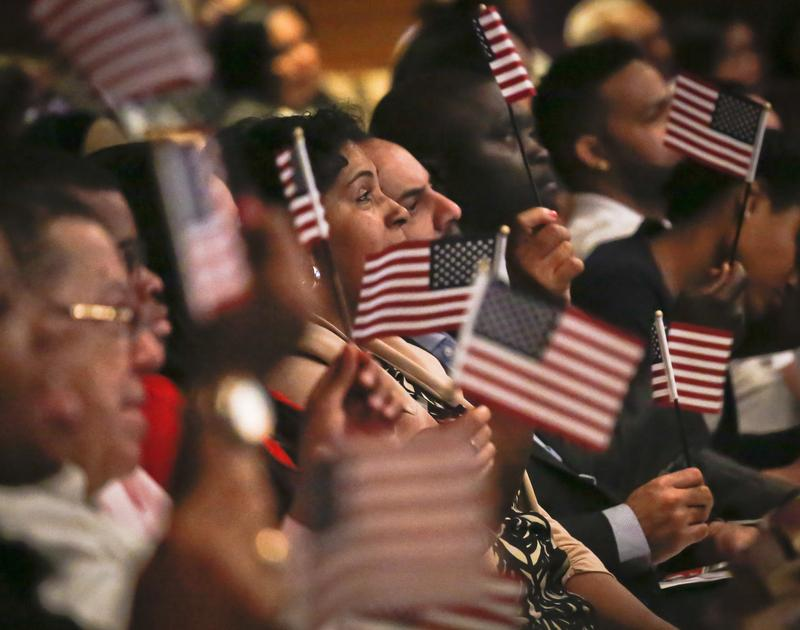 New U.S. citizens wave flags during a special Flag Day naturalization ceremony at the New York Historical Society on Tuesday, June 14, 2016 in New York.