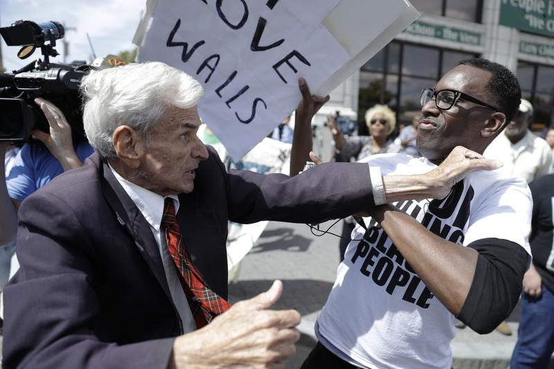 Jerry Lambert, left, a supporter of Republican presidential candidate Donald Trump, and Asa Khalif with Black Lives Matter scuffle, after Khalif took Lambert's sign, outside the location where Trump i