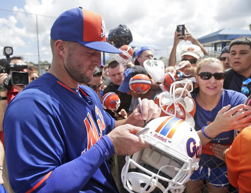 Tim Tebow, formerly an NFL player and now an MLB player, signs football helmets