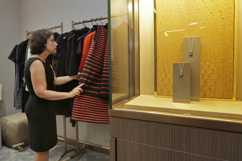In this Wednesday, Sept. 7, 2016, photo, Associated Press writer Anne D'Innocenzio looks through outfits in one of the Fifth Avenue Club's private rooms at the Saks Fifth Avenue flagship store, in NY.