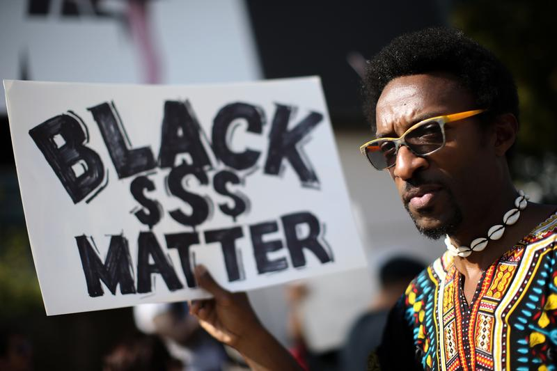 Nathaniel Dyer carries a sign during a protest near Lenox Square Mall in Atlanta.