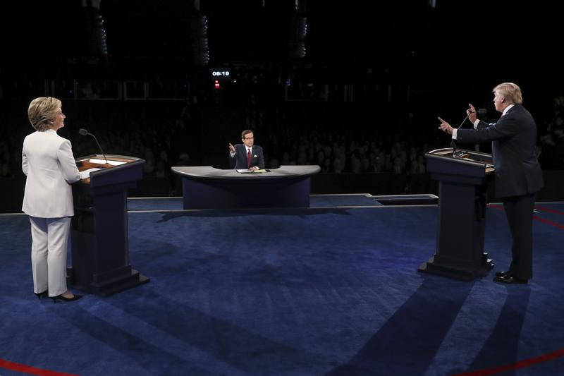 Democratic presidential nominee Hillary Clinton listens as Republican presidential nominee Donald Trump answers a question during the third presidential debate  in Las Vegas, Oct. 19, 2016.