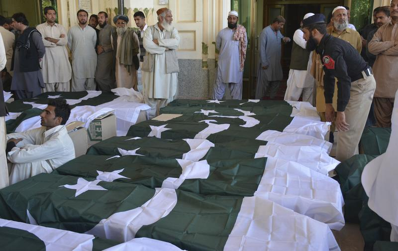 People wait to carry the bodies of their family members who died in an attack on the Police Training Academy, in Quetta, Pakistan, Tuesday, Oct. 25, 2016.