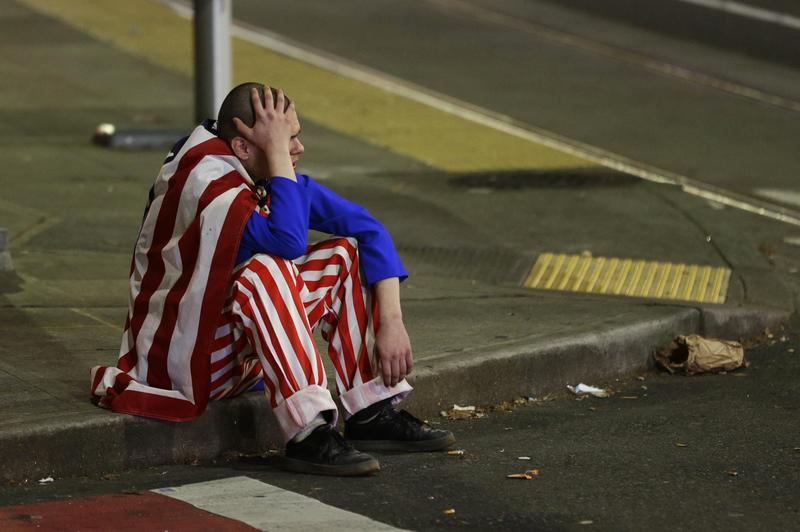 A man dressed in red-white-and-blue sits on the curb during a protest against President-elect Donald Trump, Wednesday, Nov. 9, 2016, in Seattle's Capitol Hill neighborhood.