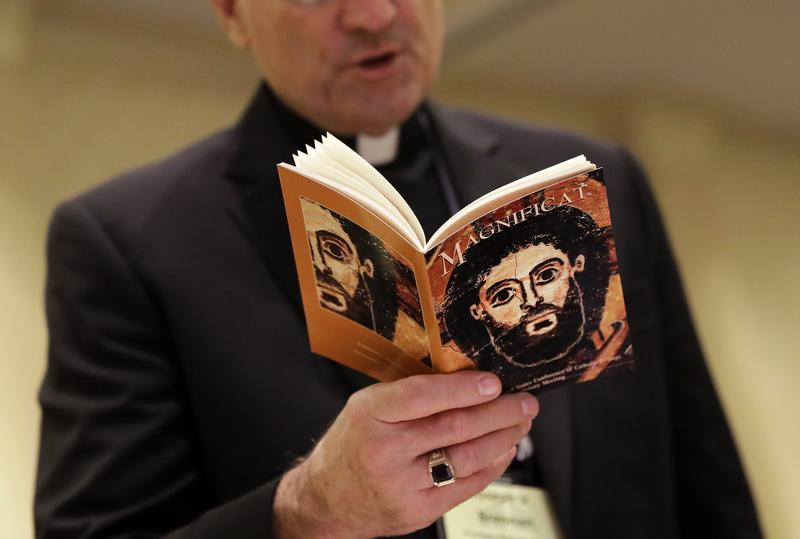 The face of Jesus Christ is seen on a booklet as Auxiliary Bishop Joseph Brennan recites a group prayer during the U.S. Conference of Catholic Bishops.