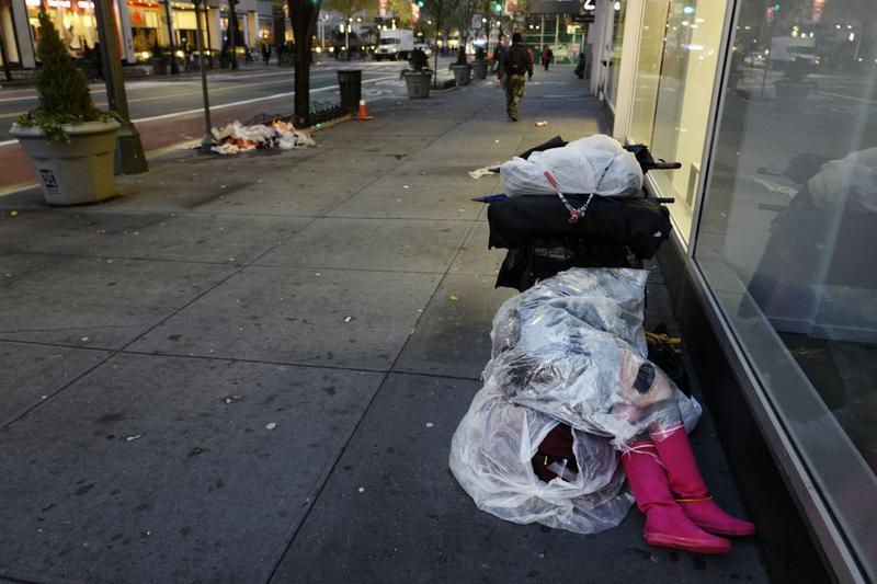 A homeless person sleeps beneath a plastic sheet on a New York sidewalk.