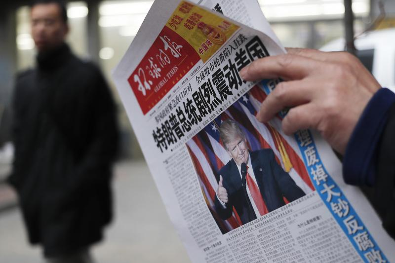 "In this Nov. 10, 2016 file photo, a man reads a newspaper with the headline that reads ""U.S. President-elect Donald Trump delivers a mighty shock to America"" at a newsstand in Beijing."