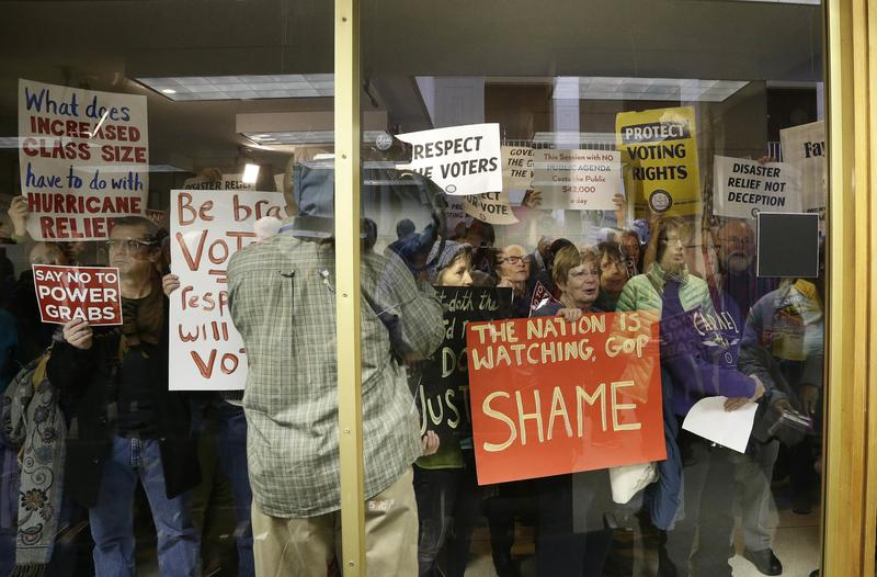 Protestors gather outside of a press conference room during a special session at the North Carolina Legislature in Raleigh, N.C., Thursday, Dec. 15, 2016.