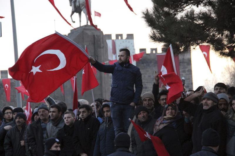 People wave national flags as they protest after a car bomb attack in central Anatolian city of Kayseri, Turkey, late Saturday, Dec. 17, 2016. More than a dozen Turkish troops were killed.