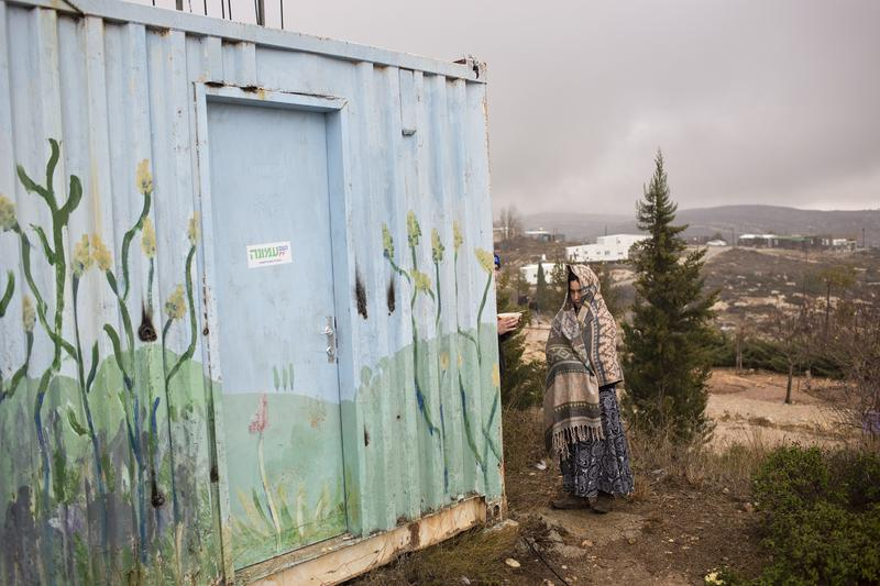 A Jewish settler covers herself from rain in Amona, an unauthorized Israeli outpost at the West Bank, east of the Palestinian town of Ramallah, Sunday, Dec. 18, 2016.
