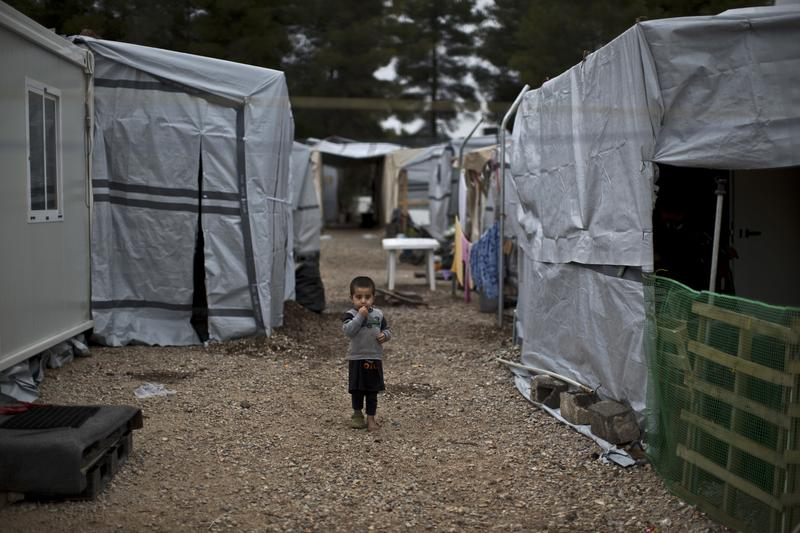 A Syrian refugee child walks between shelters at the refugee camp of Ritsona about 86 kilometers (53 miles) north of Athens, Wednesday, Dec. 28, 2016.