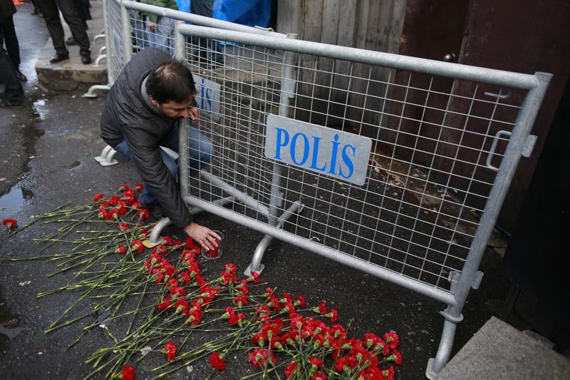 People leave flowers for the victims outside a a nightclub which was attacked by a gunman overnight, in Istanbul, on New Year's Day, Sunday, Jan. 1, 2017.