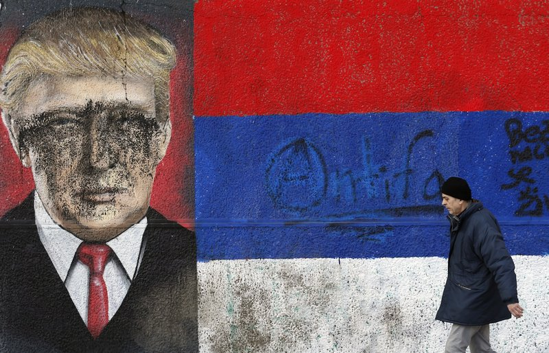 A man passes by graffiti depicting US President-elect Donald Trump vandalized with paint, in Belgrade, Serbia, Friday, Jan. 20, 2017.