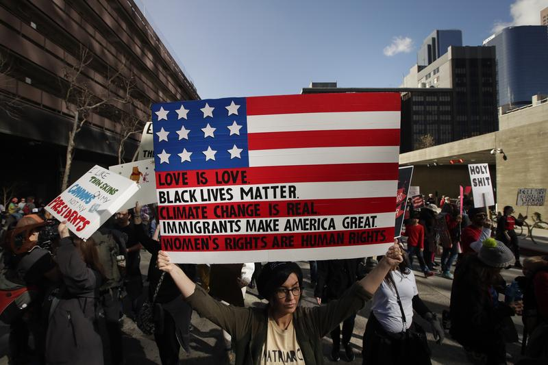 Protesters carry signs as they march along the street at the Women's March on Saturday, Jan. 21, 2017, in Los Angeles.