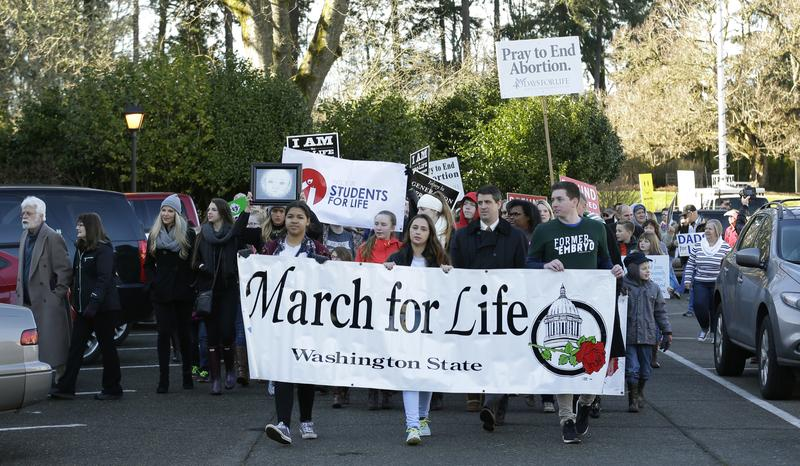 Participants in an anti-abortion rally and march carry signs and banners as they arrive at the Capitol in Olympia, Wash., Monday, Jan. 23, 2017.