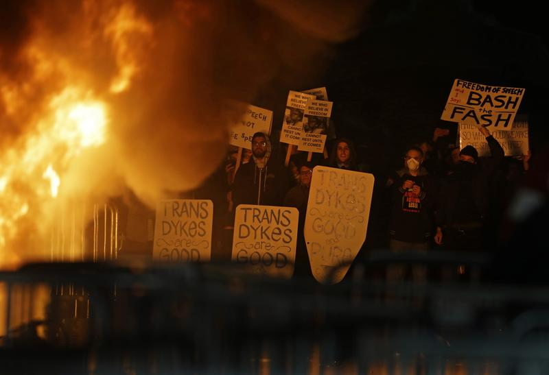Protesters watch a fire during a rally against the scheduled speaking appearance by Breitbart News editor on the U.C. Berkeley campus.