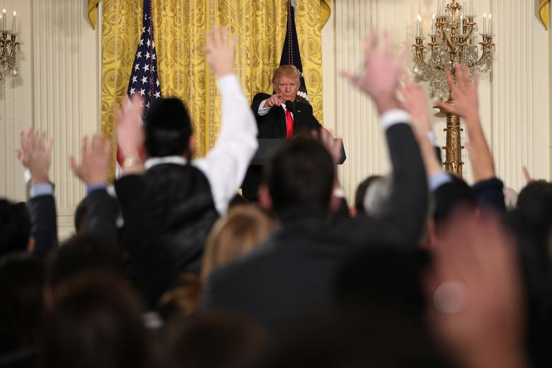 Reporters raise their hands at a news conference with President Donald Trump on February 16, 2017.