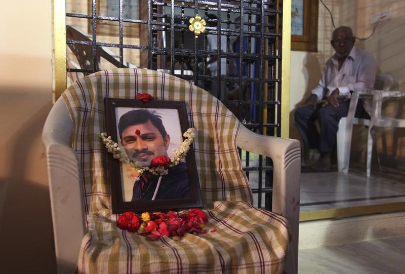A family member waits for the arrival of the body of Srinivas Kuchibhotla from the US next to a garland and photograph in his residence on the outskirts of Hyderabad, India, Tuesday, Feb. 28, 2017. A