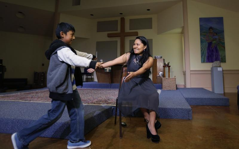 Hilda Ramirez, an immigrant living illegally in the U.S, reaches out to her son Ivan as she sits for an interview in the sanctuary at St. Andrew's Presbyterian Church, in Austin, Texas. Ramirez.