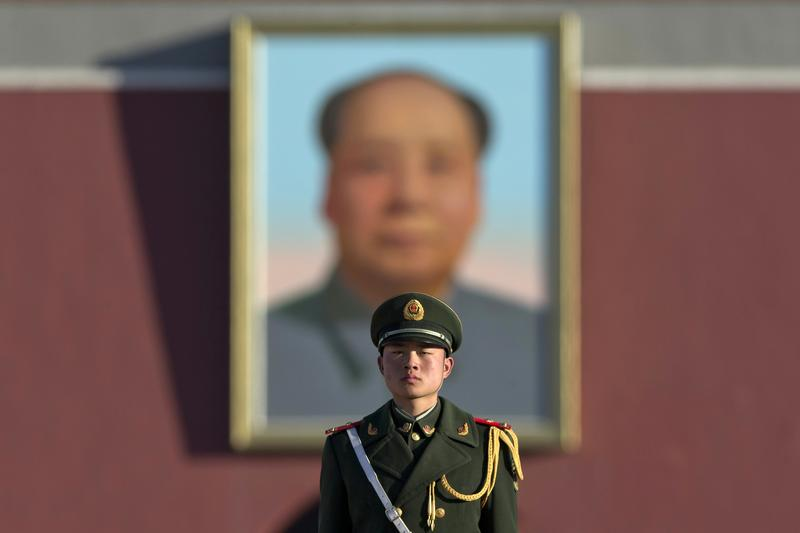 A Chinese paramilitary policeman stands on duty near former Chinese leader Mao Zedong's portrait on Tiananmen Gate near the Great Hall of the People.