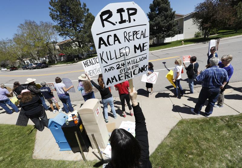 Lisa Moore of Denver holds up a sign during a protest outside the office of U.S. Rep. Mike Coffman, R-Colo., over the health care overhaul bill up for a vote in the U.S. House May 4, 2017.
