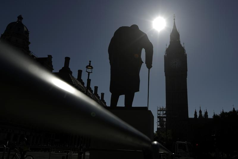 A statue of Winston Churchill stands silhouetted in front of the Houses of Parliament in London, Monday, June 19, 2017.