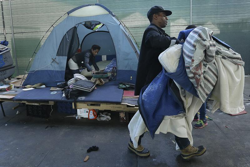 A homeless couple gather their belongings in San Francisco, Tuesday, March 1, 2016 after the city declared a large tent city a health hazard.