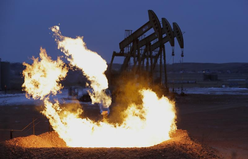 Flames erupt from a natural gas flare near oil pump jacks in the Watford City, N.D. area.