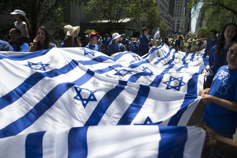 In this Sunday, June 1, 2014 file photo, revelers carry a banner made of Israeli flags as they march up Fifth Avenue during the Celebrate Israel Parade.