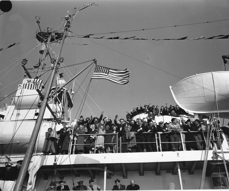 "Displaced persons wave from the deck of the ""Ship of Freedom"" as they near the pier in New York on Oct. 30, 1948"