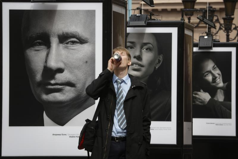 A man enjoys a drink as he walks past a portrait of Russian President Vladimir Putin displayed among portraits of Russian athletes, winners of the Sochi 2014 Winter Olympics at the photo exhibition.