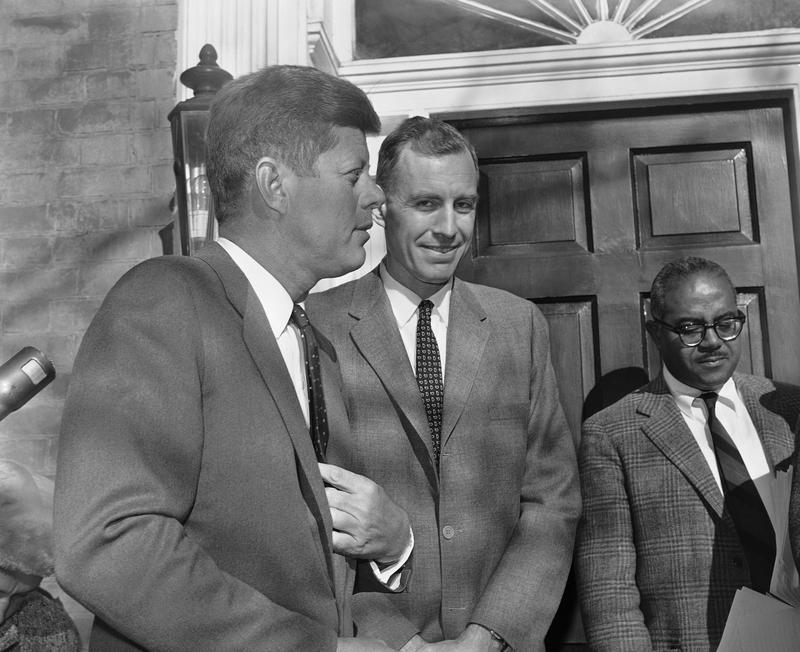 President-elect John F. Kennedy stands with David E. Bell, professor of economics at Harvard University, as he announces Bell's appointment as Director of the Budget in the new administration.