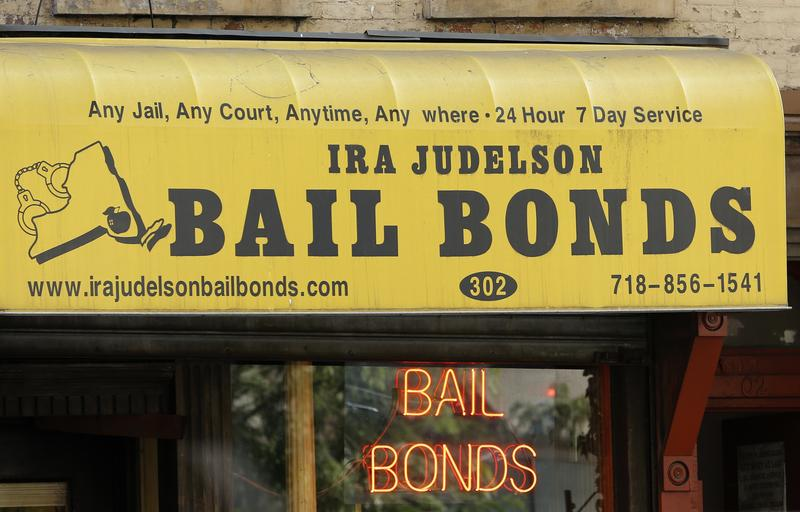 In this photo taken, Tuesday, July 7, 2015, a bail bonds business is shown along Atlantic Avenue in the Brooklyn borough of New York. Officials say they're eliminating cash bail for thousands.