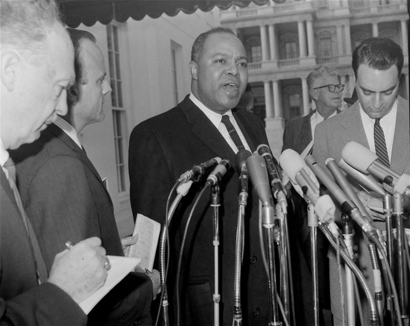 James Farmer, head of Congress of Racial Equality, talks to reporters, December 4, 1963, after conferring with President Johnson at the White House.
