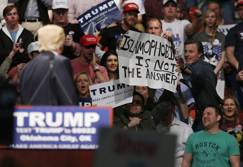 "Republican presidential candidate Donald Trump, left, looks on as a Trump supporter reaches for a sign that reads ""Islamophobia is not the answer"" at a rally."