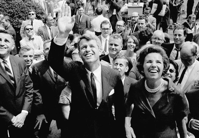 Atty. Gen. Robert F. Kennedy waves shortly after announcing he will seek the democratic nomination for the U.S. senate from New York. At right is his wife, Ethel. Kennedy.