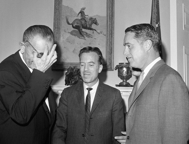 President Lyndon Johnson has a hand to his forehead at the White House in Washington on Jan. 17, 1966 with Jack Vaughn (c) and Sargent Shriver (r)..