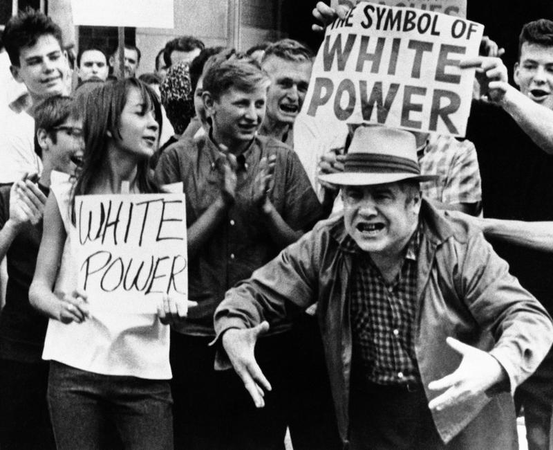 While members of crowd of onlookers display white power signs another man gestures as he expresses views to passing civil rights marchers in Gage Park area on Southwest side in Chicago. Aug. 15, 1966