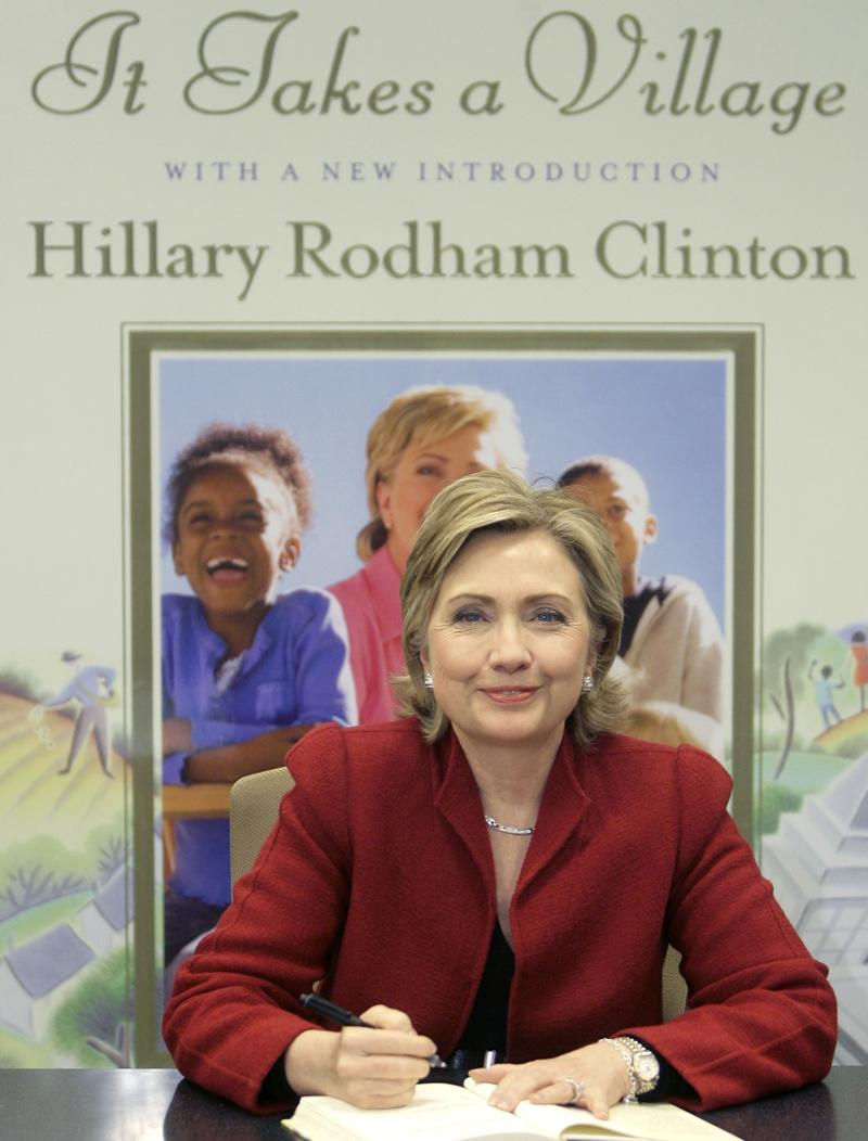 "In this Dec. 18, 2006 file photo, Sen. Hillary Rodham Clinton signs copies of the 10th Anniversary edition of her book ""It Takes a Village"" in New York."