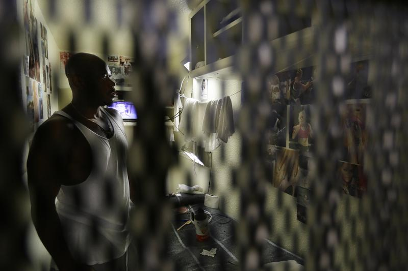 An inmate looks at photographs on his cell wall in San Quentin State Prison.