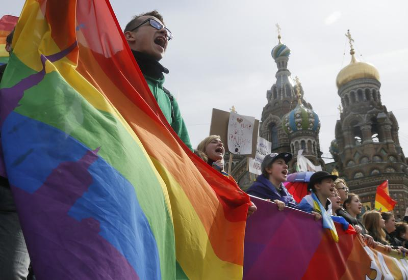 Gay rights activists shout slogans during a traditional May Day march in St.Petersburg, Russia, Friday, May 1, 2015.