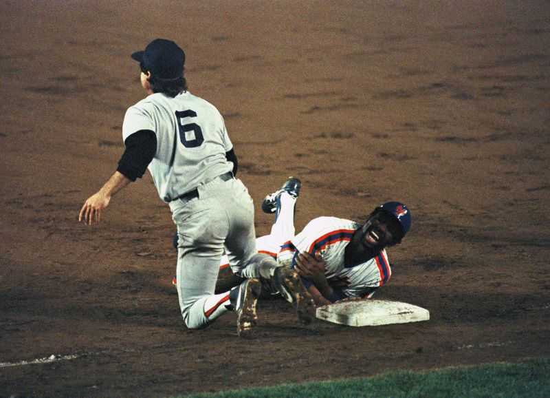 New York Mets Mookie Wilson reacts after colliding with Boston Red Sox Bill Buckner while sliding back safely to first base.