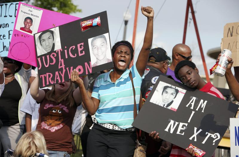 In this March 22, 2013 photo, protestors, Lakesha Hall, 32, of Sanford, center, and her son, Calvin Simms, 12, right, gather for a rally for Trayvon Martin, the black teenager who was fatally shot.