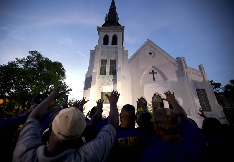 AP10ThingsToSee - Members of the Omega Psi Phi Fraternity lead a crowd of people in prayer outside the Emanuel African Methodist Episcopal Church after a memorial in Charleston, S.C. on  June 19, 2015