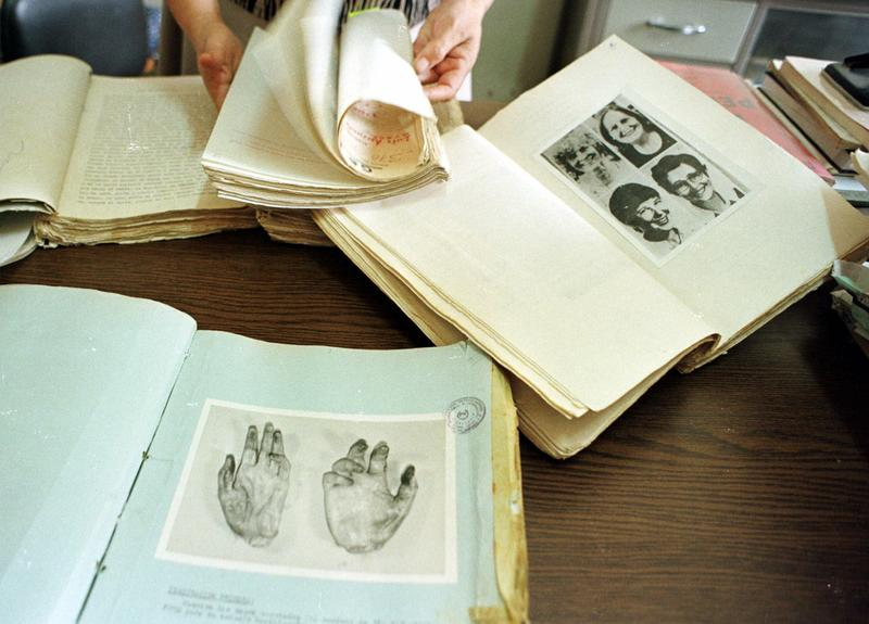 A judicial employee shows in this April 1998 photo documents of the nuns Ita Ford, Maura Clarke, Dorothy Kazel and layworker Jean Donovan who were assassinated on Dec. 1980.