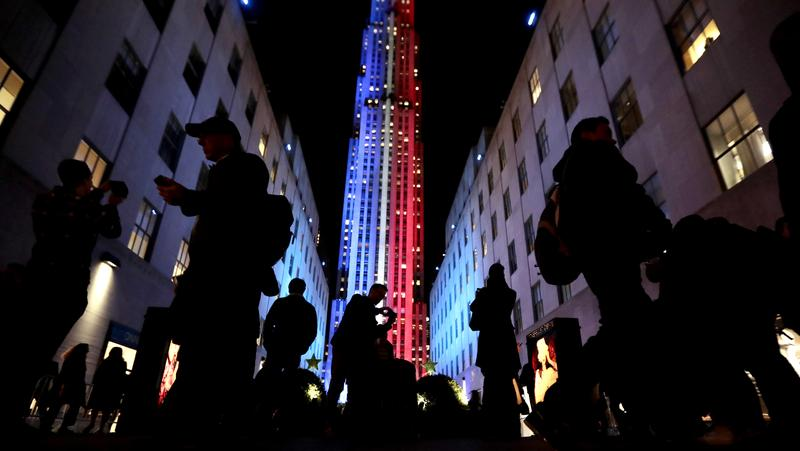 People stop for photographs in front of Rockefeller Center, which is illuminated in patriotic lights during an Election Day gathering, Nov. 8, 2016, New York